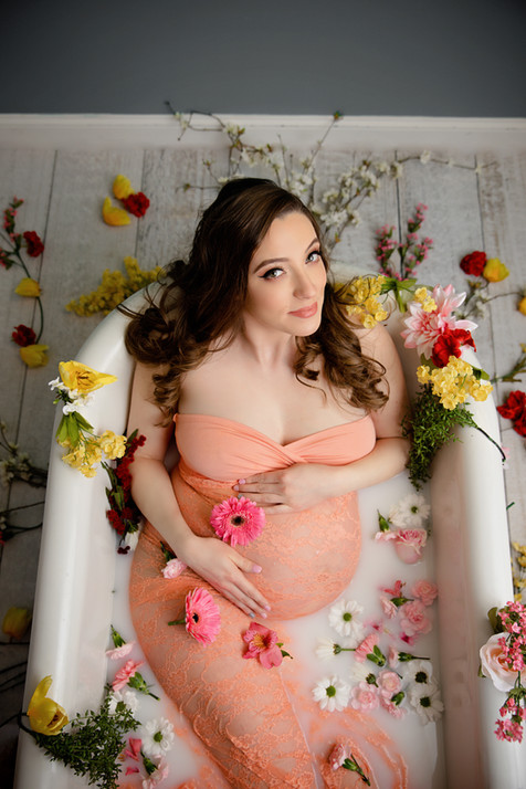 Milk bath with flowers maternity pictures in clawfoor tub.