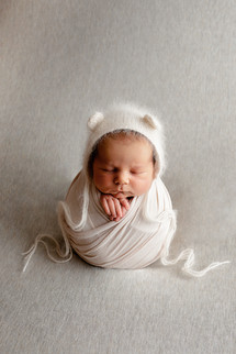 Newborn wrapped in white with a white hat with ears