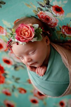 Newborn girl wearing a big flower headband on a flowered backdrop
