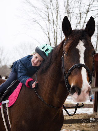 Young girl riding a horse and laying her head on the horses neck