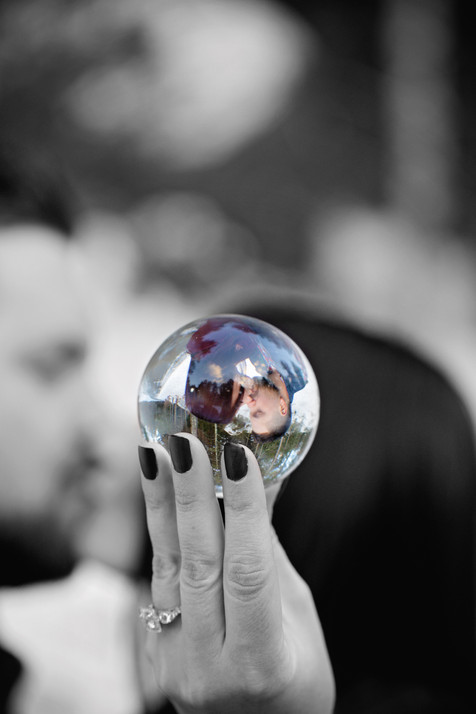 Close up on a glass ball with couple kissing in background