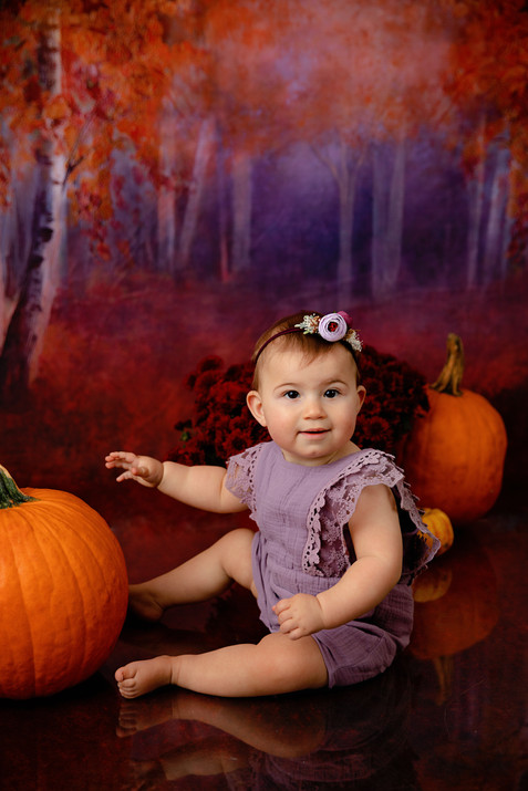 Kid wearing purple with pumpkin