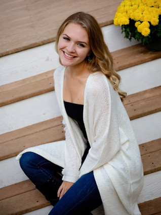 Senior girl in white shirt and jeans sitting on front steps