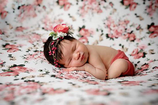 Newborn with flower backdrop and pink flower headband