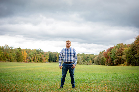 Senior guy in a field with overcast skies