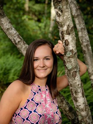 Senior Girl in pink shirt leaning on birch tree