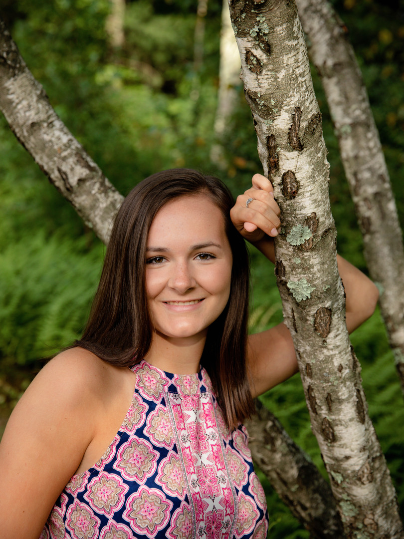 Senior Girl in pink shirt leaning on birch tree