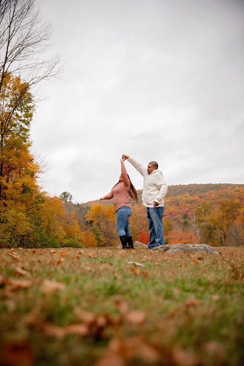 engaged couple practicing first dance with fall foliage