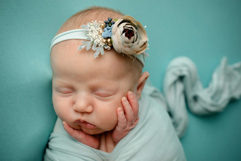 Newborn wrapped in light blue with a flower headband
