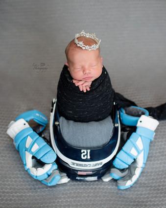 Newborn wrapped in black sat in a lacross helmet