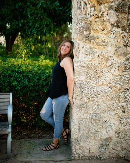 lady with back leaning against the stone wall
