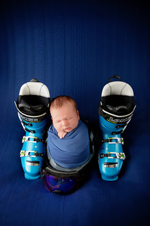 Newborn wrapped in blue between two ski shoes