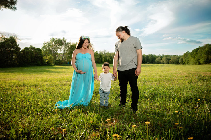 Pregnant woman in blue maternity dress holds her sons hand while he holds dads hand in a field