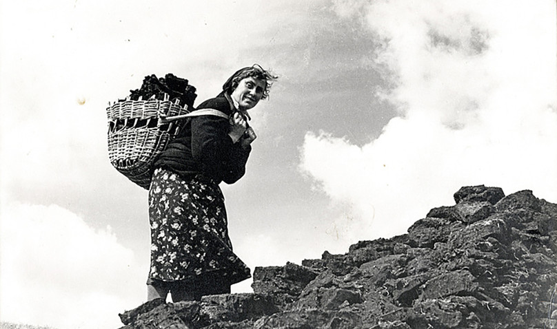 Hebridean woman carrying peat in a creel