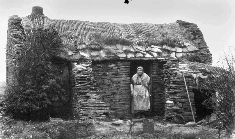 Orcadian woman beside traditional building