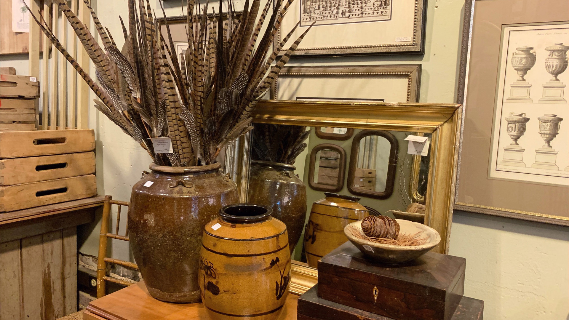 glazed pots with feathers in them, antique wood lock boxes framed prints on wall.