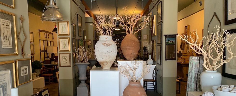 a photo of the entrance to the farmer's wife in downtown greensboro north carolina, you can see three large terra cotta urns filled with bleached branches and other antiques inside the store.