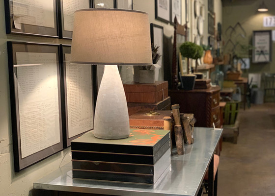 framed prints lamp sits on books on a metal top table