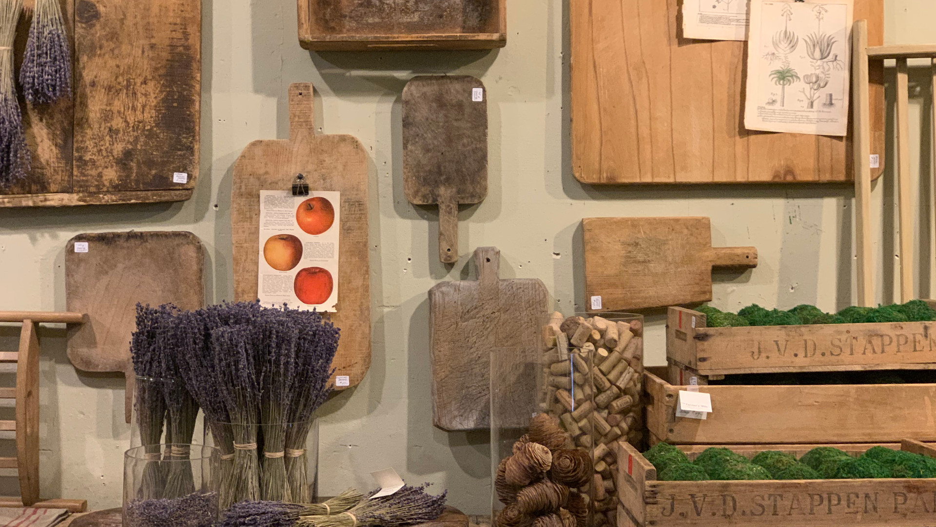 bread boards hang on a wall with wood crates filled with moss balls and dried lavendar on the table