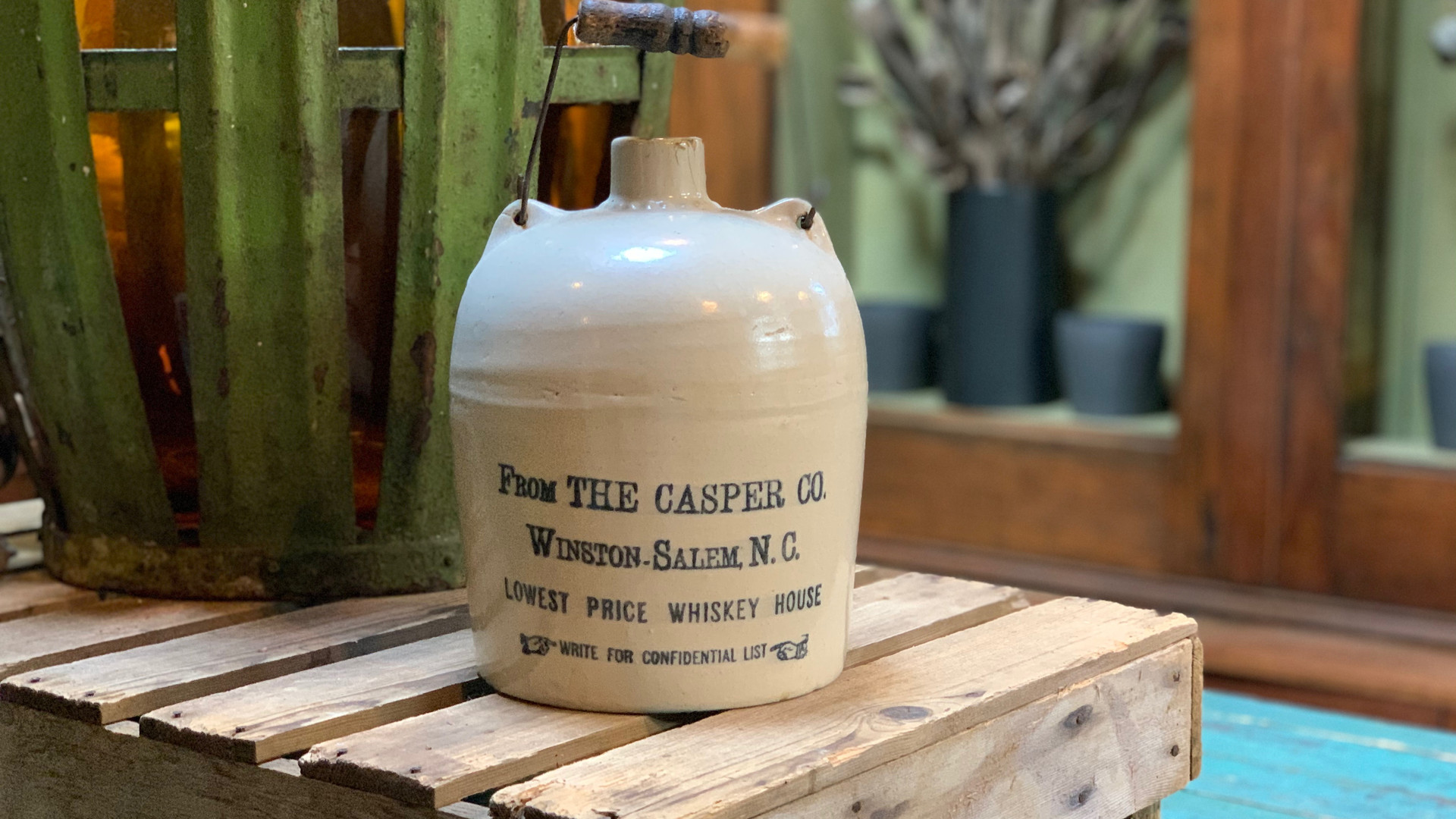 antique whiskey jug from winston salem nc sits on a wood pallet