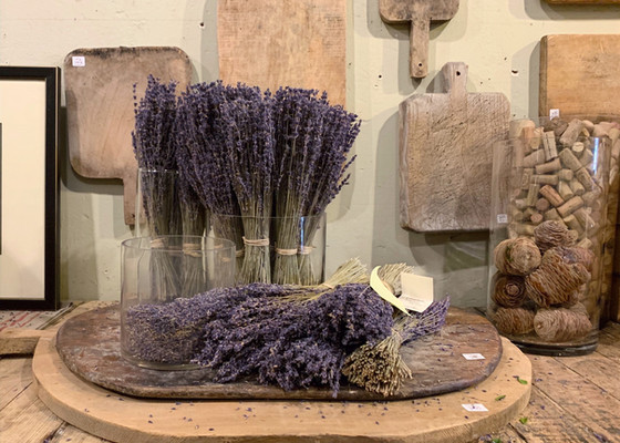 dried lavendar in a glass on a bread board with bread boards hanging on the wall