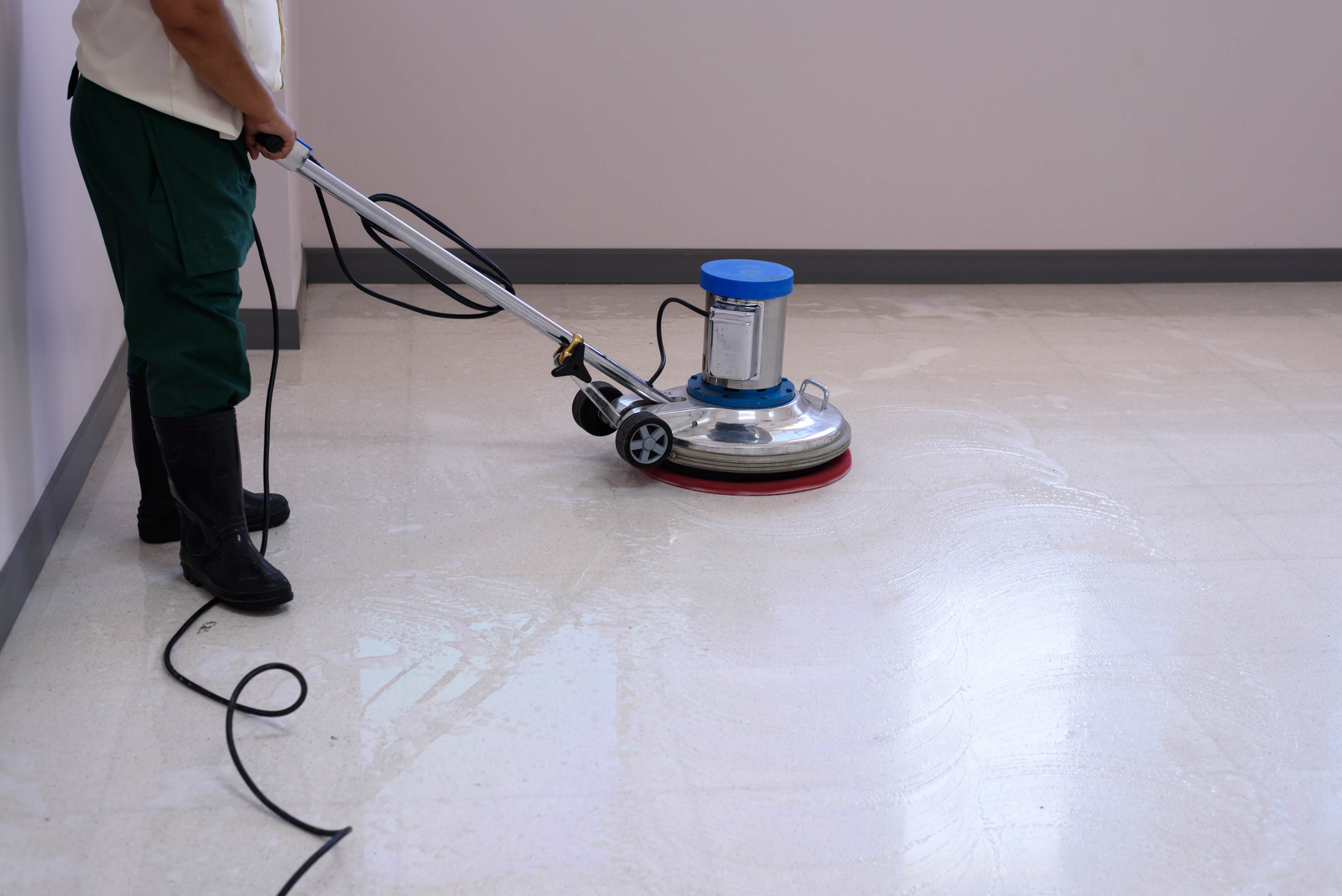 Woman maid cleaning floor with machine c