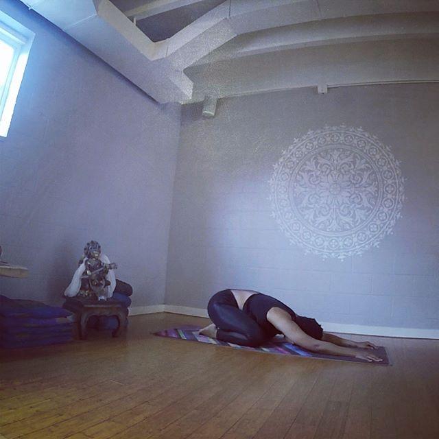 "a black woman wearing all black yoga clothing performs the yoga posture ""balasana"""