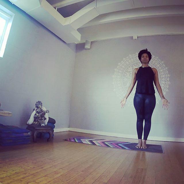 "Black woman wearing all black standing in the yoga posture ""tadasana"""