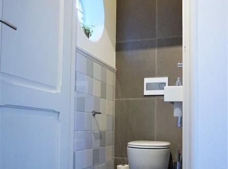 Jaren '30 toilet met gekleurde tegels en schattig rond glas in lood raampje.