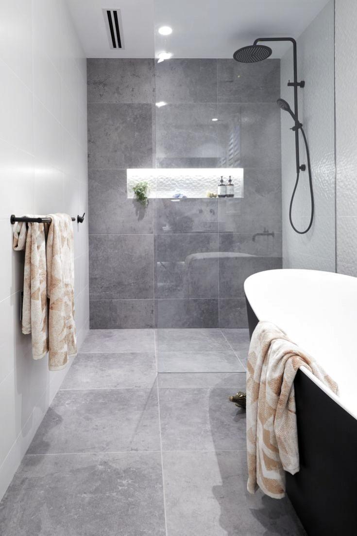 Gave industriele badkamer inspiratie met betonlook tegels, inloopdouche, opbouw zwarte regendouche en zwart vrijstaand bad