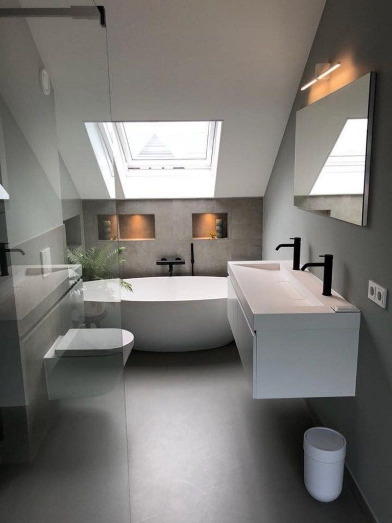Een kleine badkamer met een schuine wand, vrijstaand bad, wit badmeubel en een inloopdouche