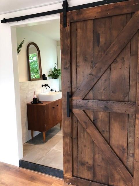 Betonlook badkamer inspiratie met grijze betonlook tegels, handvorm witte wandtegeltjes, zwarte inbouw wastafelkraan, loftdeur en wit stucwerk. Jaren '30 badkamer inspiratie.