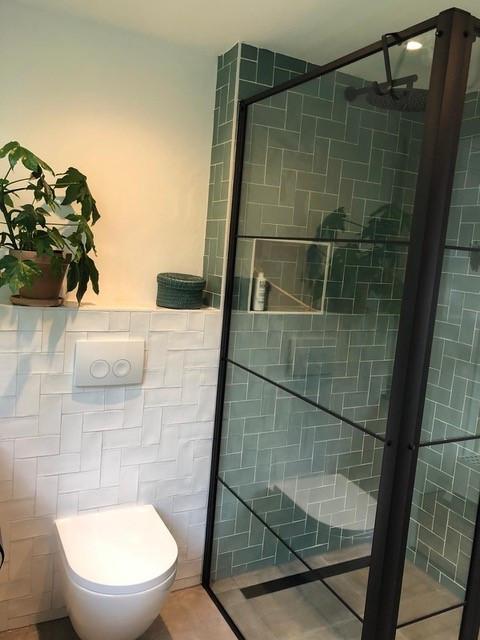 Badkamer inspiratie met betonlook grijze tegels, handvorm groene wandtegels en groene handvorm wandtegels. Zwarte douchegoot en zwarte douchecabine