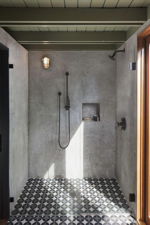 Een groen plafond, grijs beton cirré, zwarte kranen, grote douchecabine en patroon vloer tegels