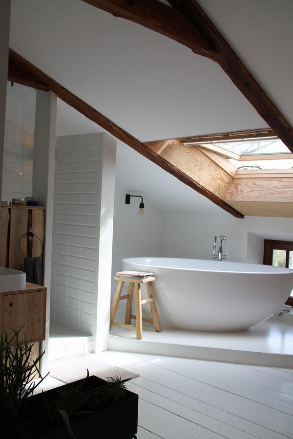 Badkamer met schuine wanden, vrijstaand bad en houten balken in de badkamer. Mooie ruime inloopdouche