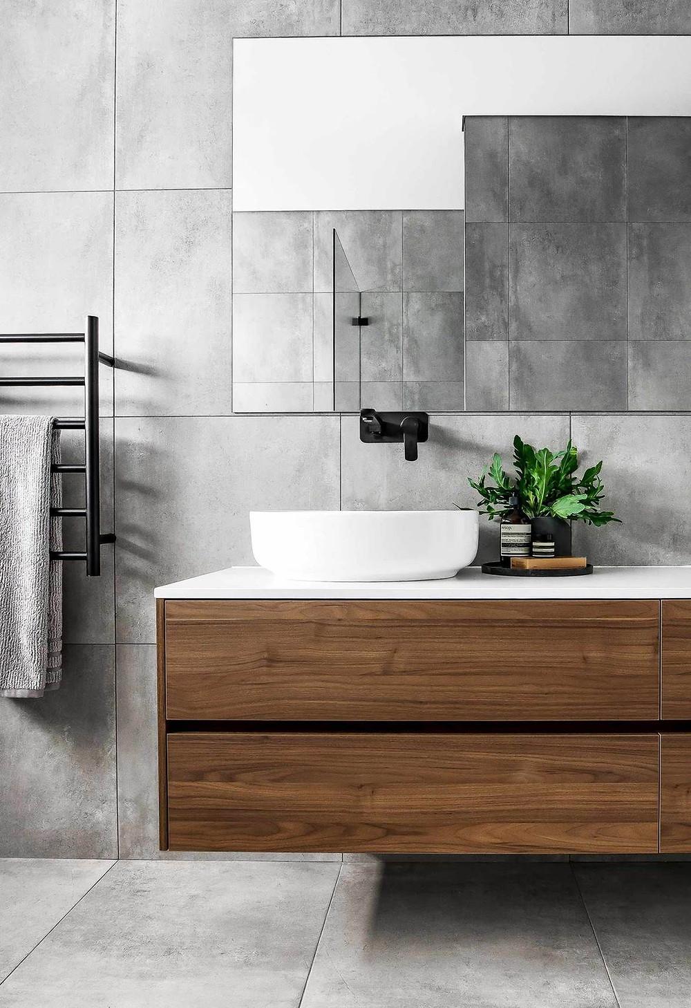 Betonlook tegels, noten houten badmeubel kast met waskom, zwarte kranen en grote spiegel van 80x120 cm.