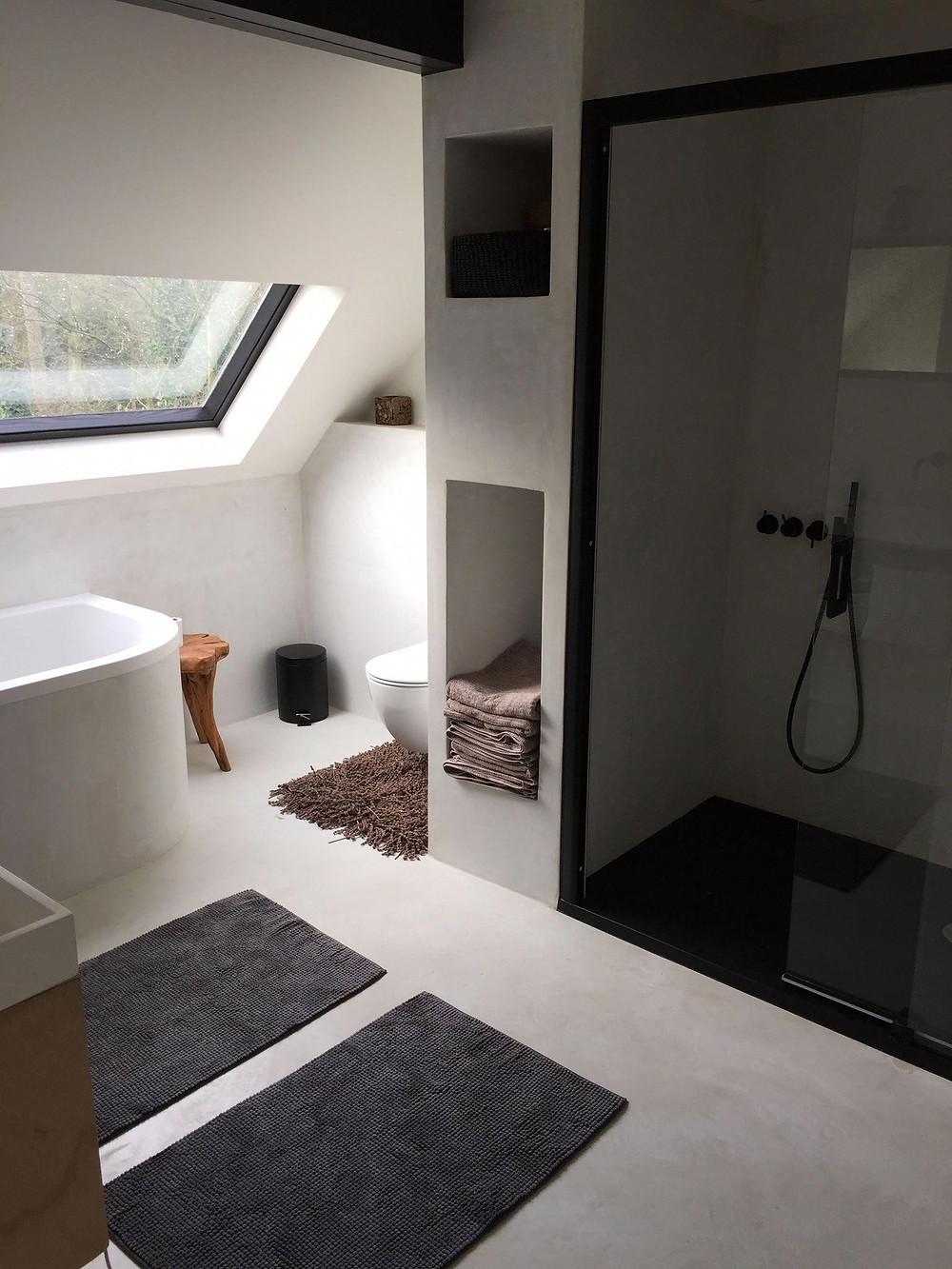 Schuine wanden, nisjes en zwart staal in deze prachtige Scandinavische badkamer inspiratie