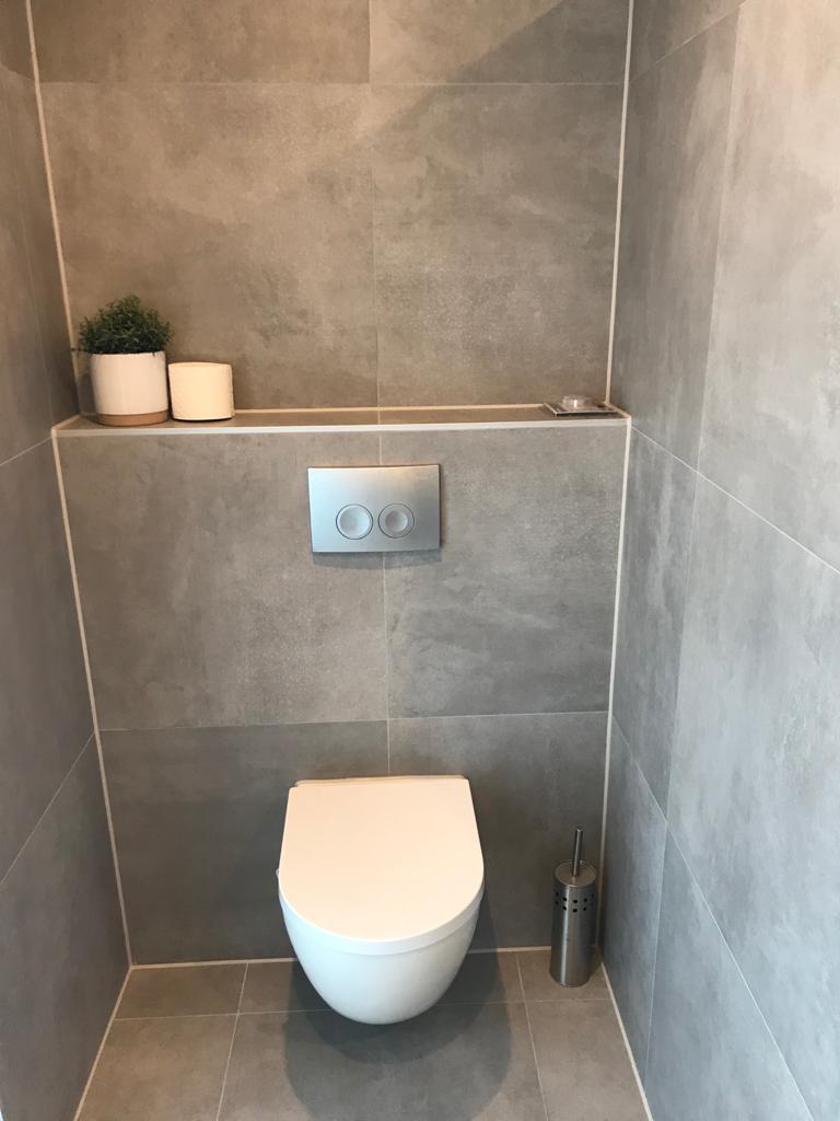 Prachtige ruime toilet met betonlook tegels in de kleur grijs