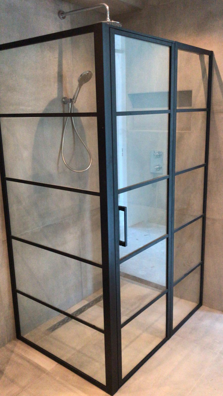 Chroom inbouwdouche, zwart stalen douchecabine en betonlook tegels in deze betonlook badkamer inspiratie