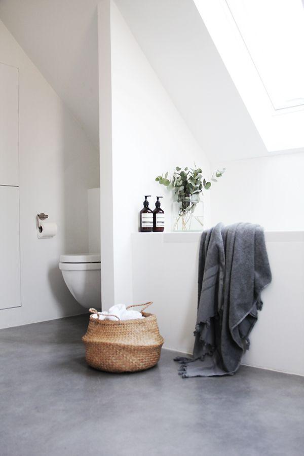 Wit met betonlook kleine badkamer met schuine wand, plant en bad