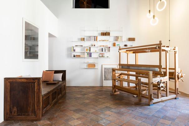 la zona living, con un telaio danese in legno, una cassapanca di recupero e la libreria string sulla parete frontale. Sospensioni disegnate da Matthew Mc Cormick
