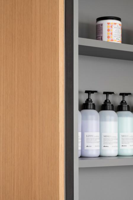 Dettaglio dell'arredo a giorno della zona lavaggio che ospita shampoo e prodotti Davines