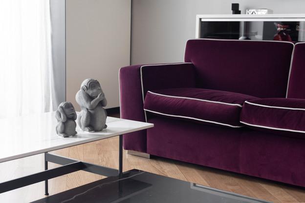 dettaglio dell'angolo tv con divani realizzati su disegno e misura in velluto dedar e tavolini su disegno