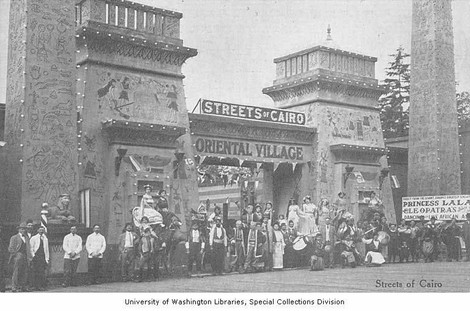 """""""Streets of Cairo and Oriental Village main entrance showing men and women dressed in costume standing in front, Pay Streak, Alaska-Yukon-Pacific-Exposition, Seattle, Washington, 1909."""""""