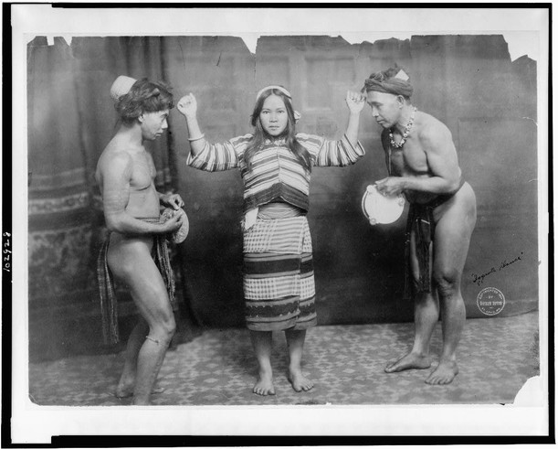 """Iggerote [i.e. Igorot] dance. Igorot woman dancing and two Igorot men with tambourines."" Gerhard Sisters, photographer"