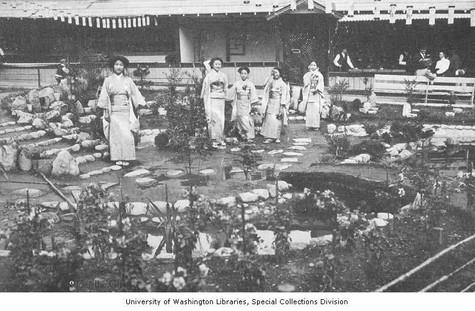 """Five women in geisha outfits standing in a garden, Japanese Village exhibit, Alaska-Yukon-Pacific-Exposition, Seattle, Washington, 1909."""