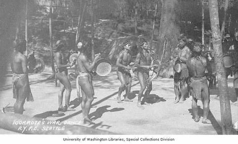 """Igorrote men performing a War Dance, Alaska-Yukon-Pacific-Exposition, Seattle, Washington, 1909."""