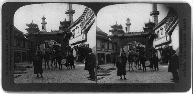 """A glimpse of Oriental life - mysterious Asia, World's Fair, St. Louis. Three women on camels, man with drum and man with horn."""