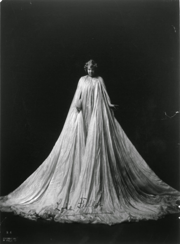 Loie Fuller, full-length portrait, standing, facing front; draped in very long gown, 1901