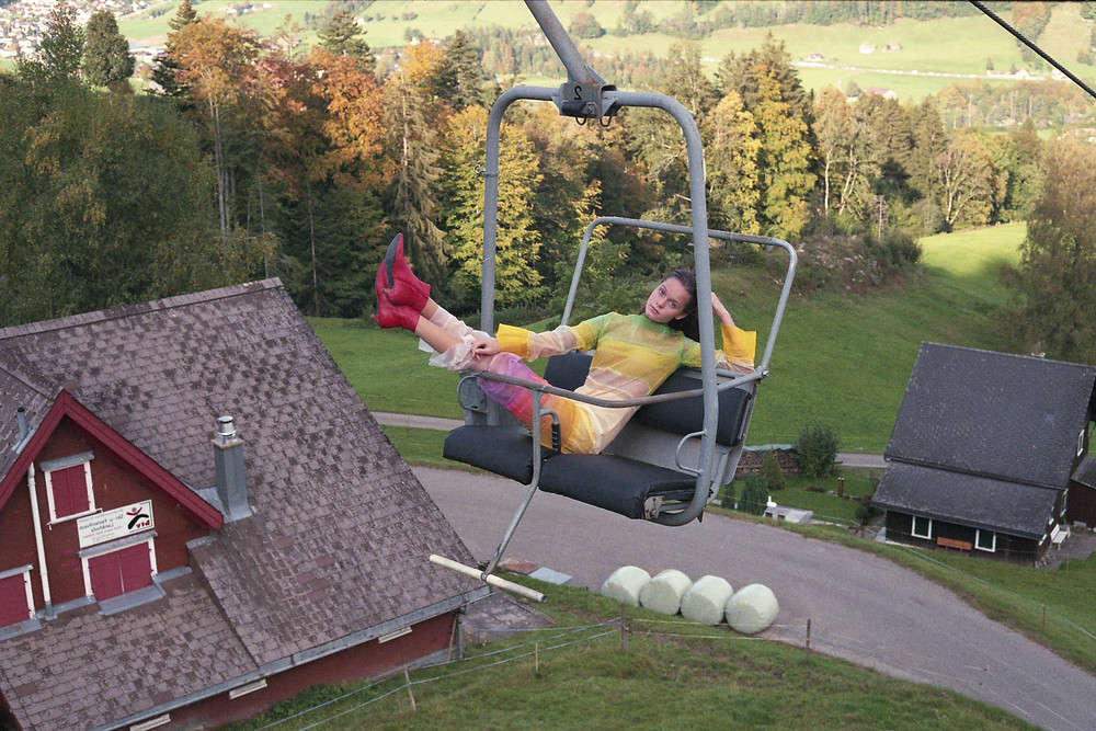 A person wearing a multicoloured dress with red kitten heel boots reclines on a ski lift above green countryside and a house with a tiled roof.